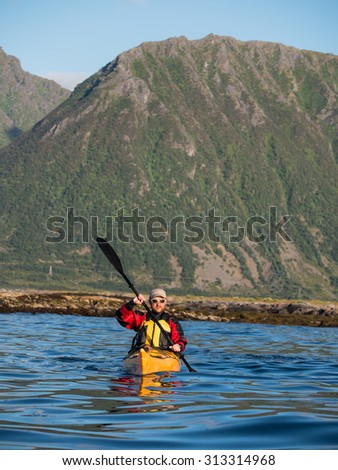 Adult male in sunglasses and baseball cap holding a paddle and rowing sitting in a kayak on the background of a large mountain  - stock photo