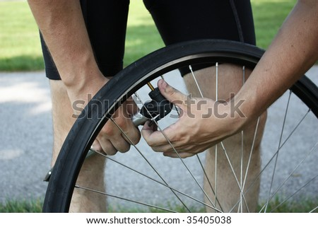 Adult male inflating tire - stock photo