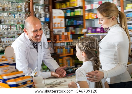 Adult male pharmacist wearing white coat standing next to shelves with medicine and helping customers
