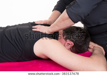 Adult male physiotherapist treating the back of a male patient.