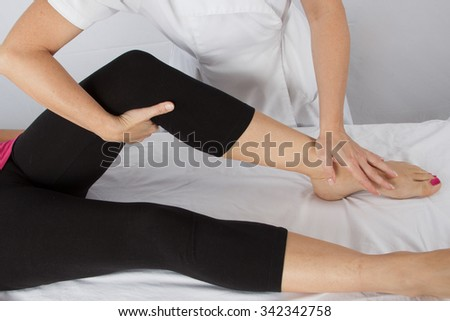 Adult male physiotherapist treating the foot of a female patient. Patient is lying on table.