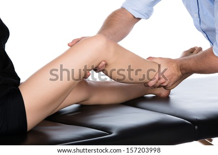 Adult male physiotherapist treating the foot of a female patient. Patient is sitting on a bed.