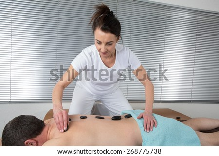 Adult male receiving hot stone therapy at spa center - stock photo