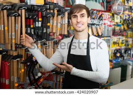 adult male seller posing at tooling section of household store
