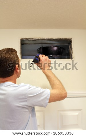 Adult male shining a flashlight into an air duct return vent to check for any need of cleaning dust or any other maintenance. - stock photo