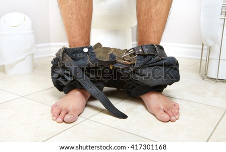 Adult male sitting on the lavatory pan. Diarrhea - stock photo