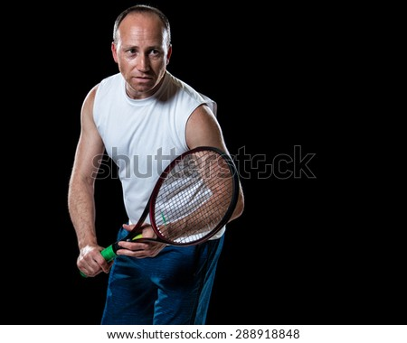 Adult male tennis player. Studio shot over black. - stock photo