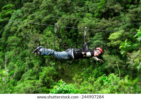 ADULT MALE TOURIST WEARING CASUAL CLOTHING ON ZIP LINE OR CANOPY EXPERIENCE IN ECUADORIAN RAIN FOREST  - stock photo