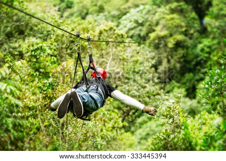 Adult Male Tourist Wearing Casual Clothing On Zip Line Or Canopy Experience In Ecuadorian Rain Forest