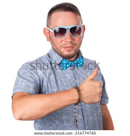 Adult male with beard in a blue bow tie in summer shirt in police handcuffs shows that he's fine on an isolated white background - stock photo