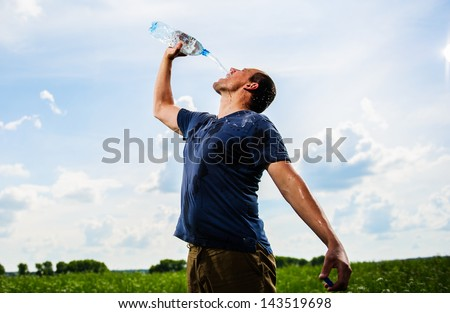 Adult mam plays with water among green field. - stock photo