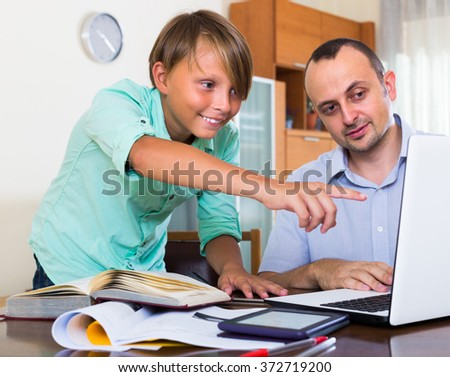 Adult man and boy studying with laptop indoors - stock photo