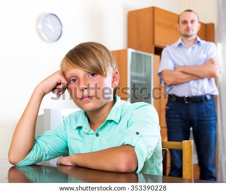 Adult man and frustrated young boy having quarrel at home - stock photo