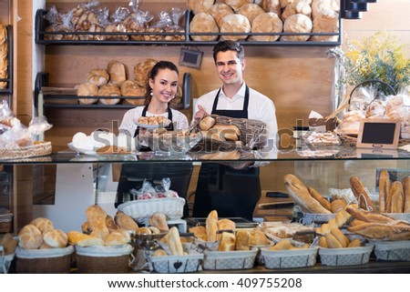 Adult man and girl selling fresh pastry and loaves in bread section
