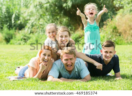 Adult man and woman with four kids lying in park on summer day