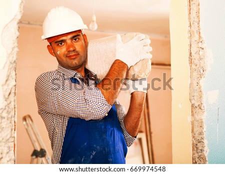 Adult man builder in gloves holding in hand package of cement