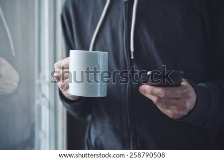 Adult Man Drinking Coffee And Texting with Mobile Phone in Morning by the Window. Selective Focus with Shallow Depth of Field. - stock photo