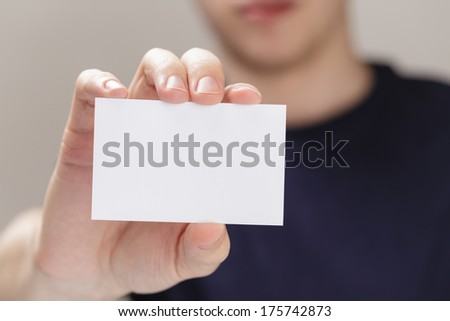 adult man hand holding empty business card in front of camera, blurred background