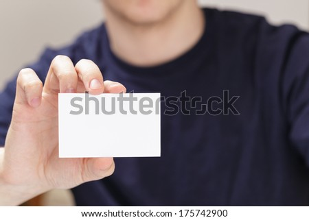 adult man hand holding empty business card in front of camera, blurred background - stock photo