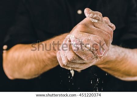 adult man hands work with flour, dark photo - stock photo
