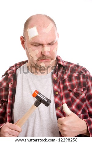 Adult man having hit his thumb with the hammer
