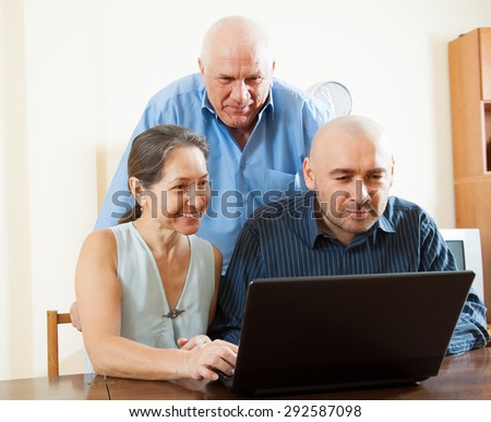 Adult man helping  for senior couple with laptop