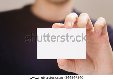 adult man hold business paper card closeup, toned photo