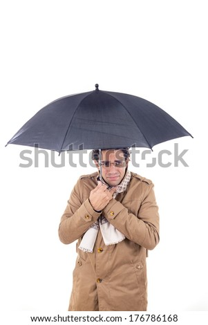 adult man in the coat with umbrella freezes