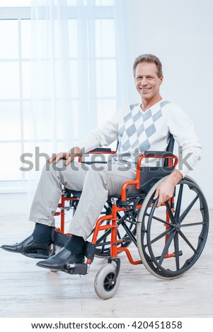 Adult man in wheelchair. White interior with big window. Man smiling and looking at camera - stock photo