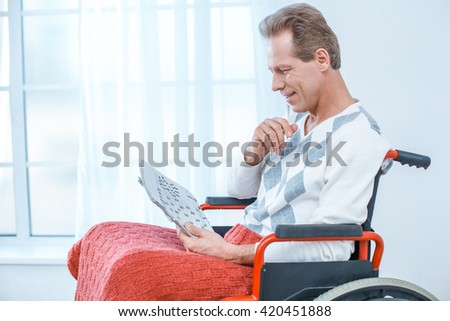 Adult man in wheelchair. White interior with big window. Man smiling and reading newspaper - stock photo