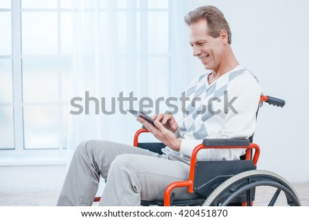 Adult man in wheelchair. White interior with big window. Man smiling and using tablet computer - stock photo