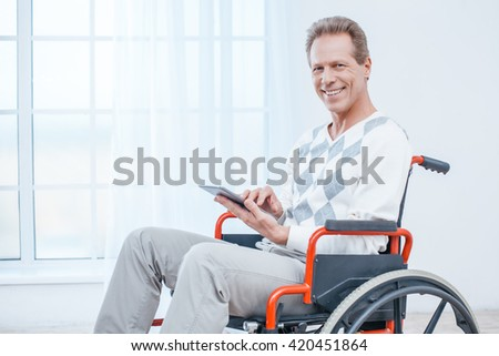 Adult man in wheelchair. White interior with big window. Man smiling, using tablet computer and looking at camera - stock photo