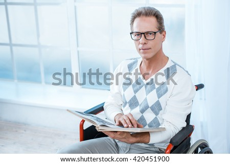 Adult man in wheelchair. White interior with big window. Man with book and glasses looking at camera - stock photo
