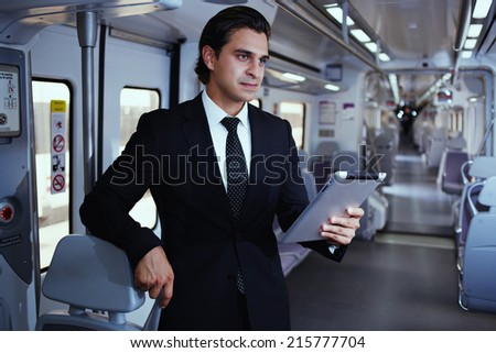 Adult man is using a Tablet PC, businessman working with tablet on the way to work, businessman holding digital tablet pc, businessman uses the new media technologies and devices to work successfully - stock photo