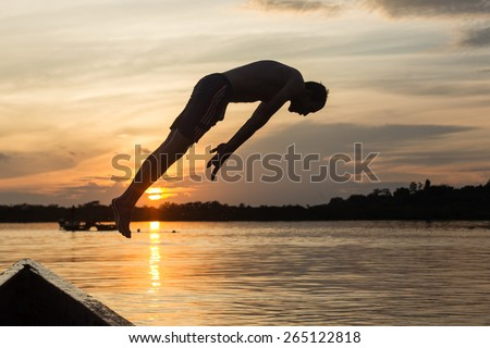 Adult man jumping into the lake against sunset - stock photo