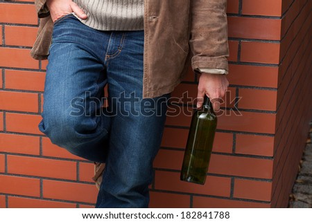 Adult man leaning on a wall and holding a bottle of wine - stock photo