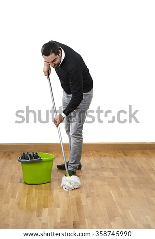 Adult man mopping the floor over white background.    - stock photo