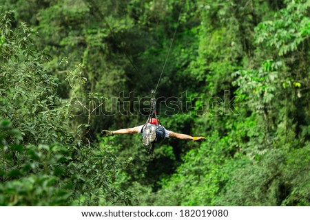 Adult man on zip line, superman position - stock photo