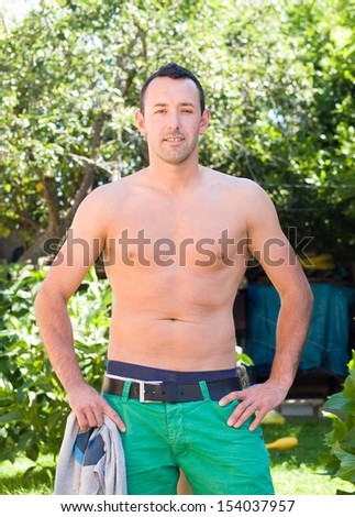 Adult man posing shirtless for a photo outdoors
