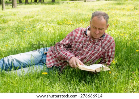 Adult man reading a book with enthusiasm - stock photo