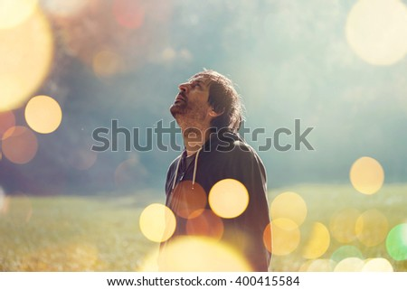 Adult man resting after jogging in the park, standing and looking up to sky, retro toned image with selective focus and bokeh light - stock photo