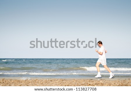 adult man running on the beach on a sunny day.