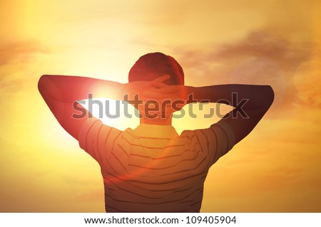 Adult man satisfied with nature beauty of sunset. Photo from behind against the sun