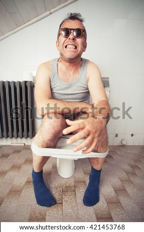 Adult man sitting on a toilet bowl in bathroom