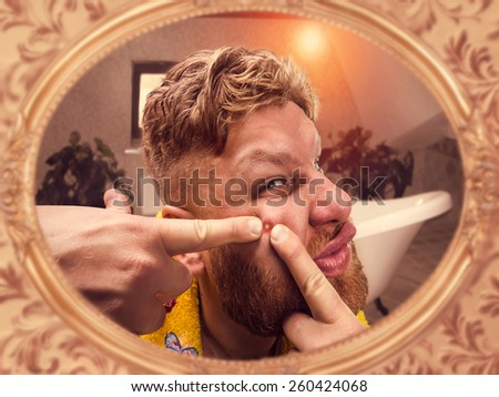 Adult man squeezes the pimple on his face - stock photo