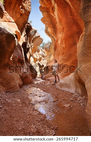 adult man standing in a slot canyon and looking upward