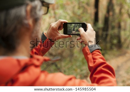 Adult man taking a picture with smart phone. Outdoor shot in nature. Shallow depth of field. - stock photo