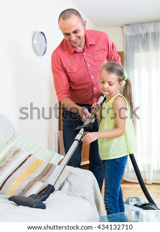 Adult man teaching cute little girl vacuuming during clean-up at home. Focus on girl