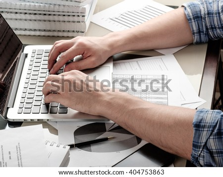 Adult man typing on laptop on glass table in home office and paperwork