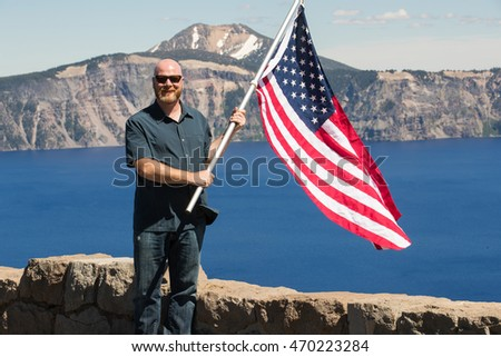 Adult man waving American flag at Crater Lake, Oregon USA